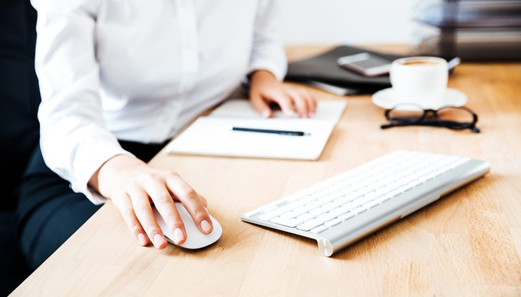 Cropped image of women's hands using keyboard and mouse